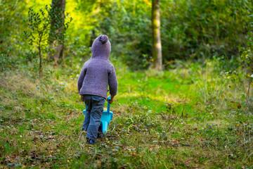 un petit garçon pousse sa brouette sur un chemin dans le forêt