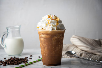 caramel frappuccino with wipped cream on marble table
