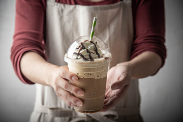 barista serving coffee frappuccino in plastic cup