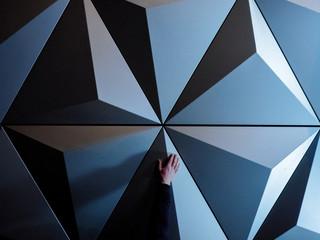 Man's hand touching geometric wall