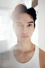Close up of young man wearing white tank top
