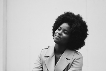 Smiling woman with afro sitting with eyes closed