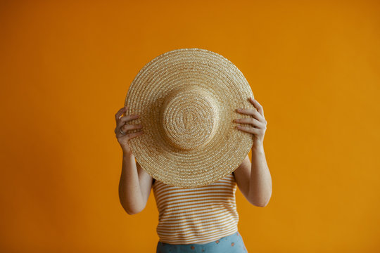 Woman holds up a straw hat in front of face