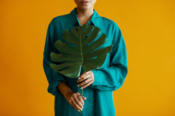 Midsection of woman holding monstera leaf