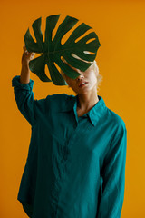 Women holds a monstera leaf in front of face