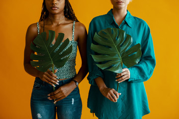 Two women hold monstera leaves