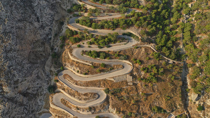 Aerial drone top down photo of snake serpentine narrow road leading uphill
