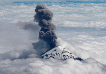 A general view shows the Popocatepetl volcano spews a cloud of ash high into the air as is pictured from a plane during a flight to Mexico City