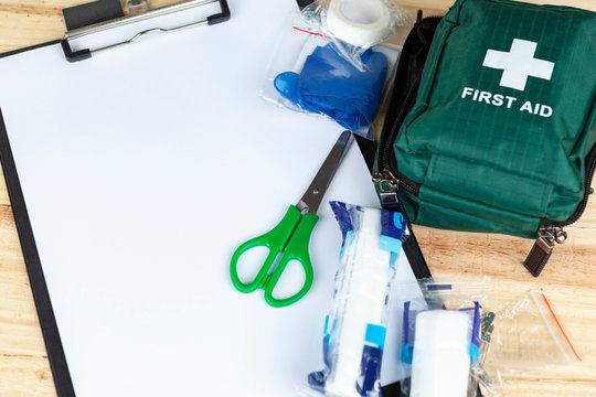 Green first aid kit on a table with a clipboard
