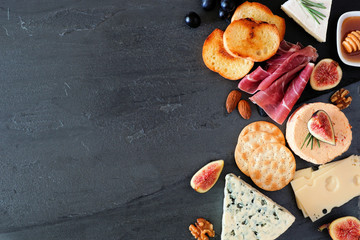 Appetizer of assorted cheeses and cured meat. Side border, top view on a dark background with copy...