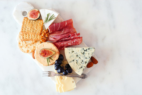 Appetizer platter with assorted cheeses and cold cut meats. Top view on a white marble background.