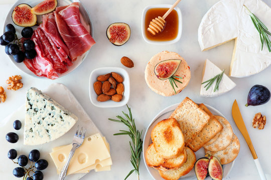Assorted cheeses and deli meat appetizers. Above view table scene on a white marble background.
