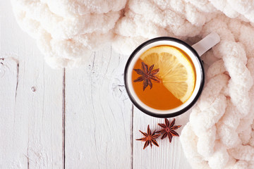 Lemon spice tea, top view on a white wood background with blanket. Cozy fall or winter theme.