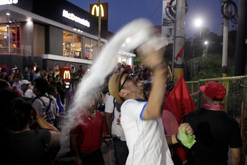 """A demonstrator throws a plastic bag with white powder during a protest against the government of president Juan Orlando Hernandez, whose brother Juan Antonio """"Tony"""" Hernandez was found guilty of U.S. drug trafficking charges, in Tegucigalpa"""