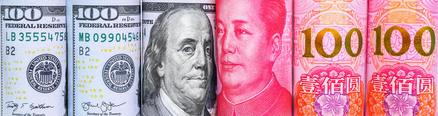 Close up rolls 100 US dollar and 100 Chinese yuan renminbi banknotes background,banner size