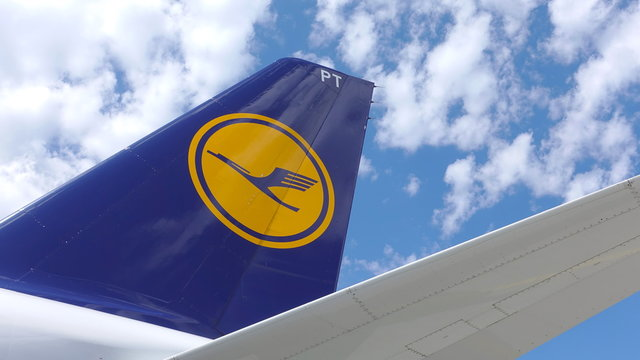 Close up of the tail fin of a Lufthansa commuter plane with the Lufthansa logo against a blue sky with clouds. Photo taken in Frankfurt, Germany - June 13, 2019.