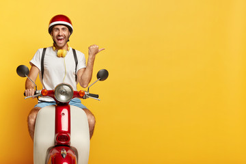 Happy man rides fast motobike, shows direction away, points thumb right on blank space over yellow background, dressed in casual wear and helmet, uses headphones, has cheerful face expression