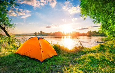 Photo sur Aluminium Camping Orange tent on the lake at sunset