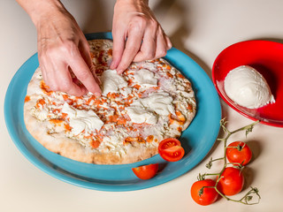 The preparation of a perfect Italian pizza with a female hand that adds all the ingredients