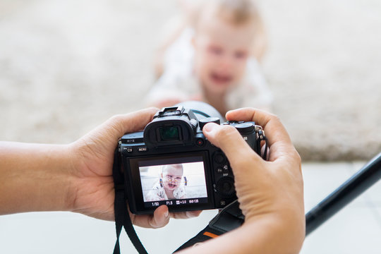 Photographer taking a picture of a cute baby