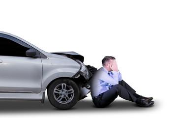 Sad businessman near a damaged car on studio