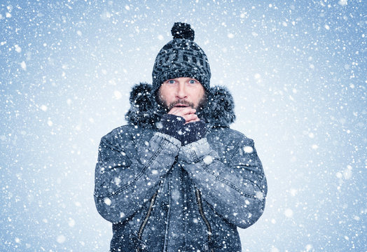 Frozen bearded man in winter clothes warms his hands, cold, snow, frost, blizzard