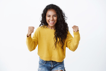Encouraged and motivated cute african-american woman in yellow sweater raising hands up, fist pump from happiness, smiling hear good news, celebrating victory, winning huge bet, white background