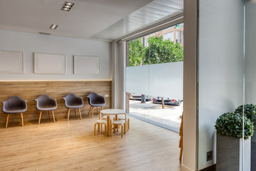 Modern design reception with gray chairs, pictures, white walls. Chairs and tables for children. Wooden floor and glass to the outside. Dental clinic.