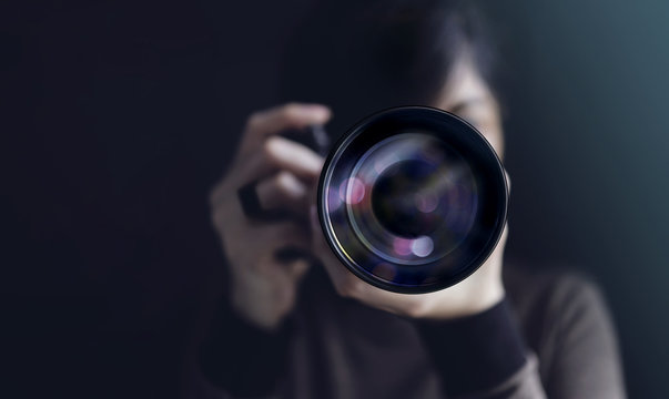 Photographer Taking Self-Portrait. Woman using Camera to Taking Photo. Dark Tone, Front View. Selective focus on Lense. Straight into a Camera