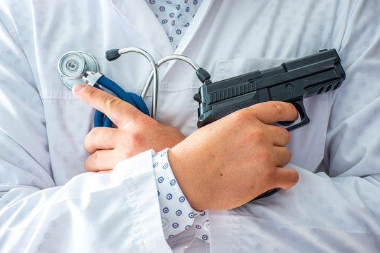 Doctor standing and holding gun in one hand and stethoscope in other with his hands crossed on his chest. Concept photo of medical errors, improperly prescribed treatment, your money or your health