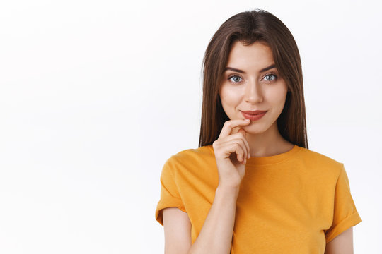 Pensive good-looking daring young modern woman in yellow t-shirt smiling sassy and creative, touching lip have interesting idea, intrigued with promo, standing white background thinking