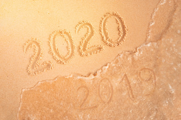 number of the new year written in sand, on tropical beach. Change numbers 2019 to 2020. New year holidays on a tropical island. The sea wave washes away the inscription 2019.