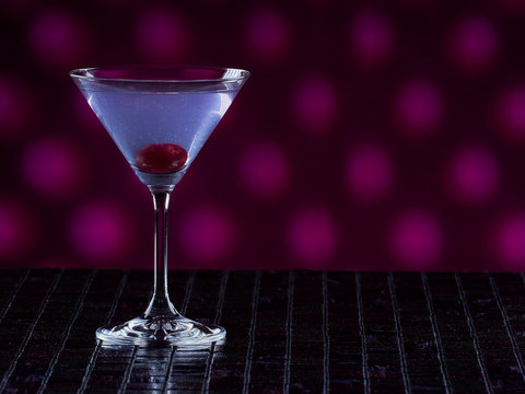 Aviation cocktail on pink dotted background, copy space on the right side