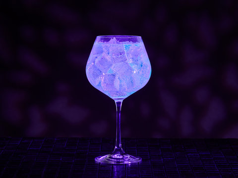 Gin tonic under blacklight (UV) illumination. Glow in the dark drink.