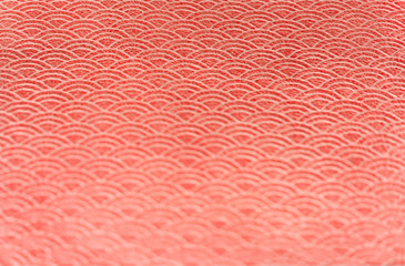 A Japanese greeting card with a traditional lace circles motif pattern on a red cloth background.