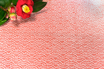 A Japanese greeting card with Tsubaki flower also called the winter rose on a traditional lace circles motif pattern on a red cloth background.