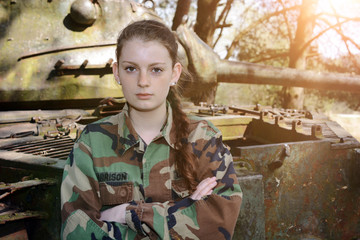 Young soldier in military army clothes with camouflage spots posing in front of a tank