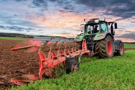 farmer plowing his fields at dusk