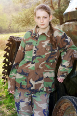 Girl in military uniform with camouflage spots posing in front of a tank