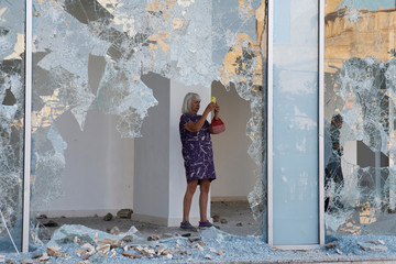 A woman takes pictures as seen through the shattered glass of a damaged shop in Beirut