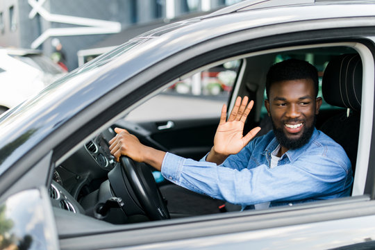 Young handsome african man wave greetings to someone while driving his car