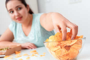 Breaking Diet. Chubby girl sitting at kitchen table eating chips excited close-up blurred background