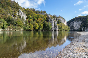 Danube valley at Danube breakthrough near Kelheim, Bavaria, Germany in autumn with gravel bank  and water reflections of limestone formations