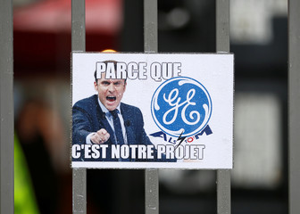 A poster with a picture of French president Macron is seen on a gate of the site of the energy branch of U.S. conglomerate General Electric in Belfort