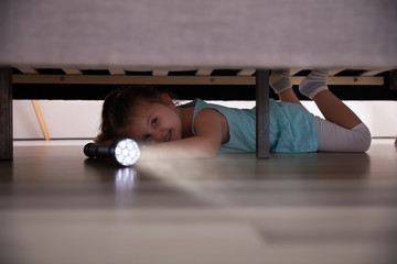 Little Girl Looking Under The Bed With Flashlight