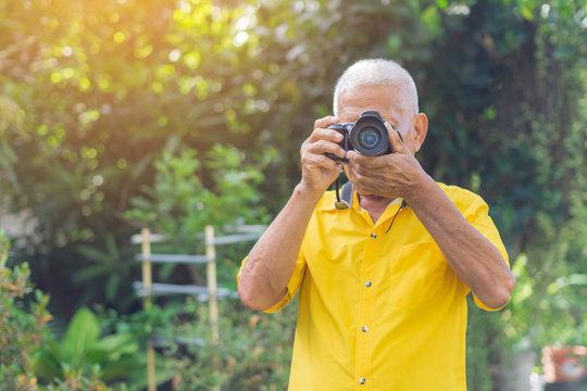 Senior man using a camera to take photo