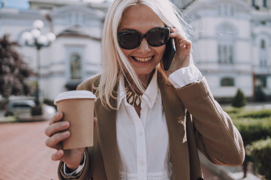 Happy pretty lady is holding mobile phone
