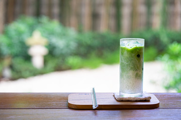 Glass of Iced matcha latte tea with milk on wood table