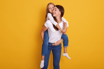 Studio shot of beautiful young brunette mother holds on back her cute little blonde daughter in white shirt and overalls, female dresses t shirt and jeans, posing isolated over yellow background.