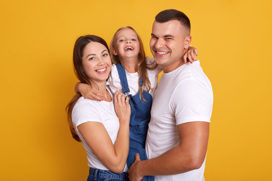 Horizontal shot of happy family with one child, looking smiling directly at camera, posing isolated over yellow studio backgroung, wearing white casual t shirts. Togetherness and happyness concept.